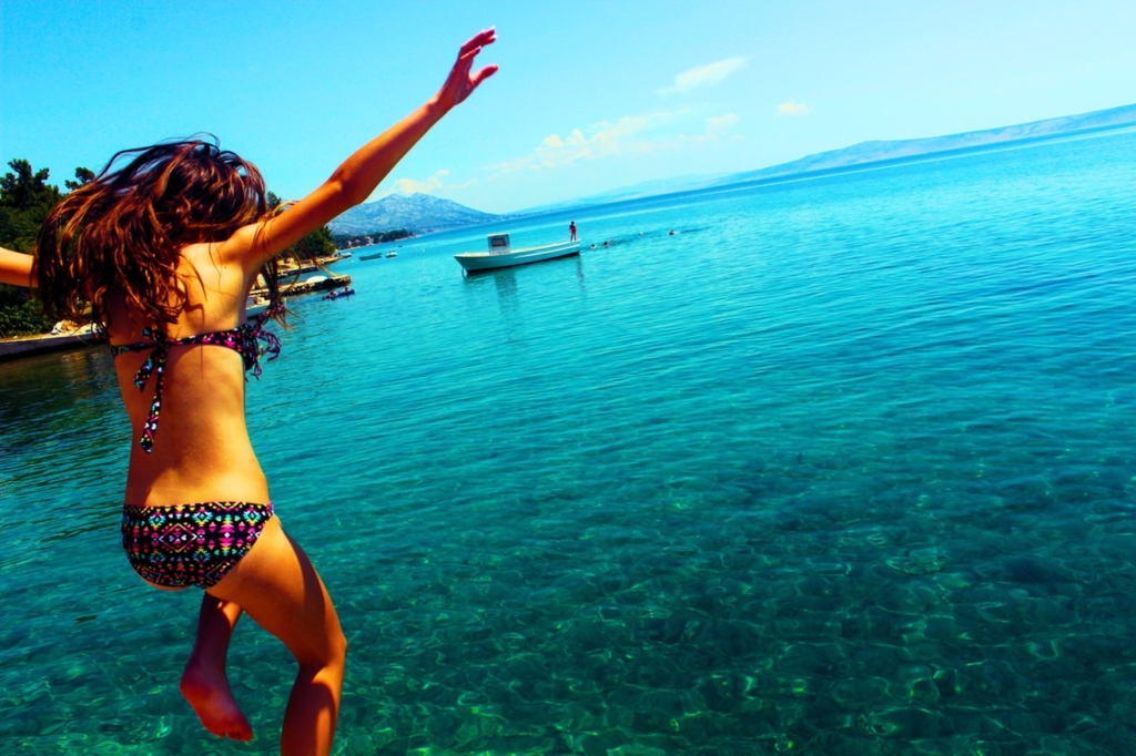 une jeune femme en maillot saute dans la mer